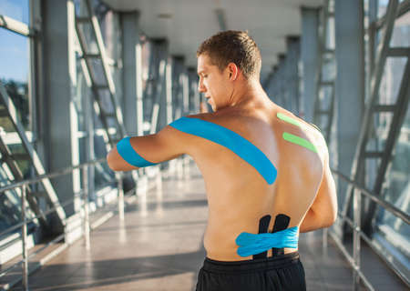 Man with kinesiology taping on back posing indoors.