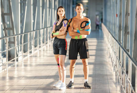 Young sports couple with kinesiological taping posing indoors.