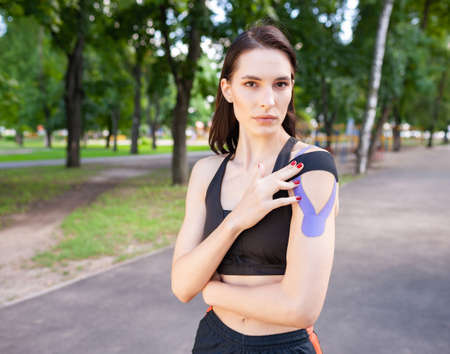 Muscular woman putting kinesiological taping on shoulder outdoors. 版權商用圖片