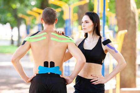 Athletes with kinesiological taping posing outdoors. 版權商用圖片