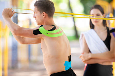 Man and woman with kinesiological taping training outdoors. 版權商用圖片