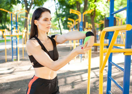 Woman with kinesiological taping stretching at sports ground.