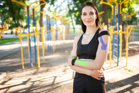 Fit woman with kinesiological taping posing outdoors. 版權商用圖片
