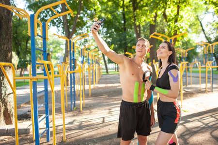 Sports couple with kinesiological taping taking selfie outdoors.
