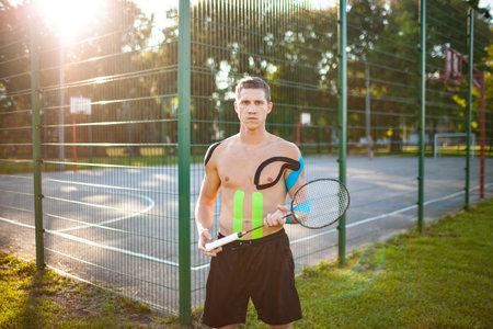 Athlete  taping posing  racket outdoors.