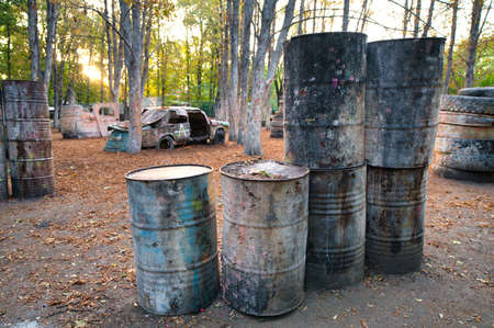 Many old round barrels at the base for playing paintball, behind which the players excited by the game are hiding