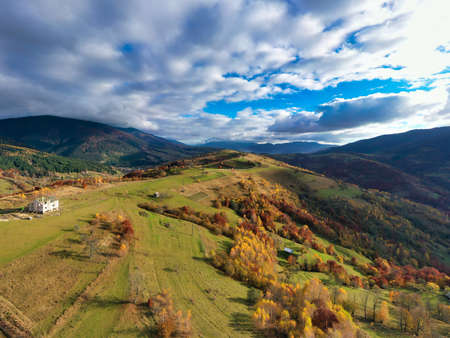 Sky with white and fluffy layer of clouds over green autumn hills, Aerial panoramic drone shot