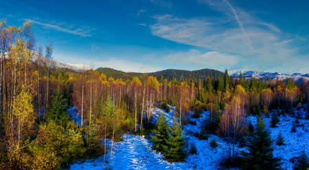 Picturesque mountain landscapes of autumn with snow near the village of Dzembronya in Ukraine Carpathians mountains.
