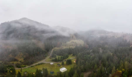 Rainy foggy and gray weather in the mountain valley of the Carpathians in Ukraine in small village Aerial panoramic drone shot