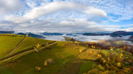 Autumn flight through blue sky in Carpatian autumn mountains, Aerial panoramic drone shot