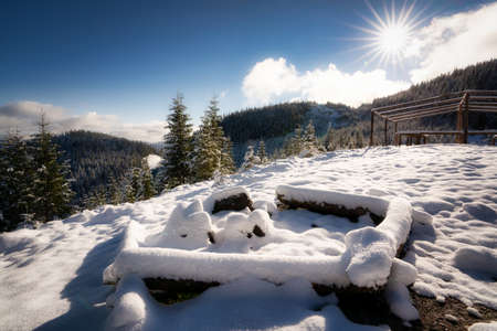 A large snow-covered campfire site for hiking in the Carpathian mountains I bright cold sun