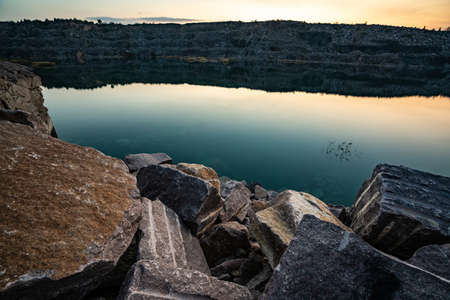 Beautiful lake surrounded by large piles of stone waste from hard work in a mine against a beautiful night sky with stars Zdjęcie Seryjne