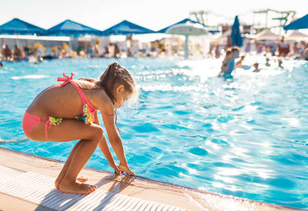 Little girl stands by the pool and tries the water with her hands