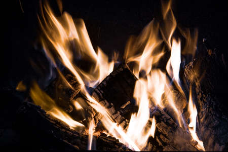 Fiery yellow orange tongues on dark background rise up in a brick fireplace burning flame, cold toned