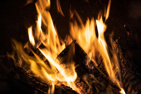 Fiery yellow orange tongues on dark background rise up in a brick fireplace burning flame, fire close-up photo Banco de Imagens