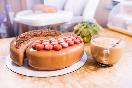 On an old wooden table there is a beautiful mousse chocolate cake with a transparent large cup with aromatic coffee and houseplant