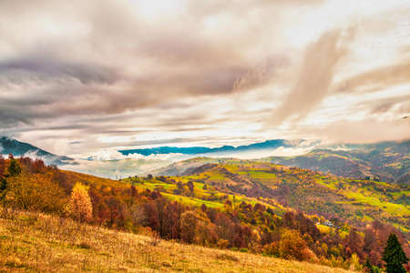 Unusually beautiful nature of the Carpathian mountains in beautiful hills, fantastic sky of colorful forests and a small village Stock Photo
