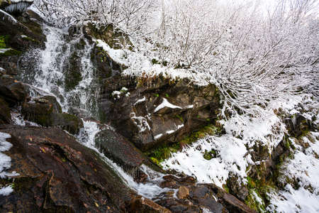 Small stream among wet stones and white snow in the picturesque Carpathian mountains in Ukraine