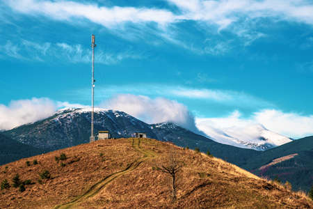 Telecommunication tower against the backdrop of an awesomely beautiful sky with blurry snow-white clouds