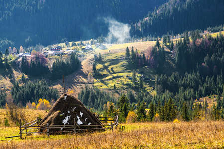 A large haystack against the backdrop of the wonderful nature of the Carpathians and the extraordinary sky