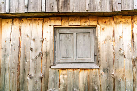 Small closed window in the wooden wall of an old house Standard-Bild