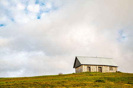 A lonely gray house stands on a wet green meadow among thick gray fog