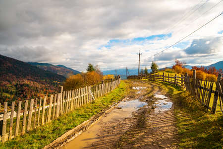 A path along the ridge of a hill with a large puddle and an old fence against the backdrop of a colorful forest Standard-Bild