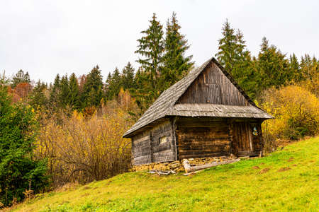Old house in a small valley with green meadows and colorful forests