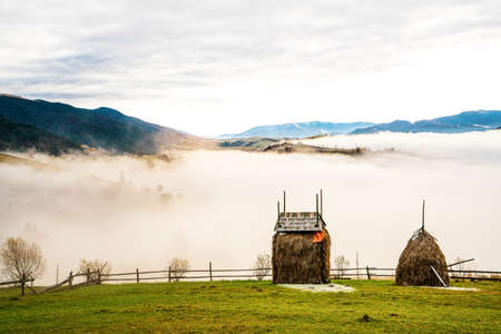 Several haystacks in a thick white fog against the backdrop of a bright sun