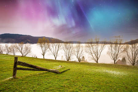 A large tack stands on a green field among the dense gray fog and purple sky with stars