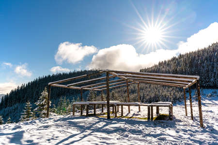 The gazebo on the top of the mountain stands in a snow-covered meadow, bathed in the light of the bright cold sun