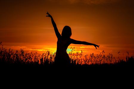 Una giovane ragazza che balla in un campo tra l'erba, con le mani in alto, contro un bel cielo con nuvole e il sole che sorge al tramonto, la sagoma di una donna in alto contrasto