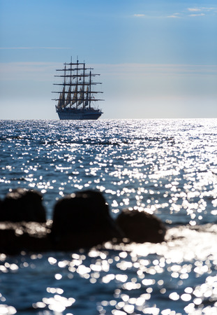 The worlds largest sailing ship with five masts leaves at sunset in the open sea.