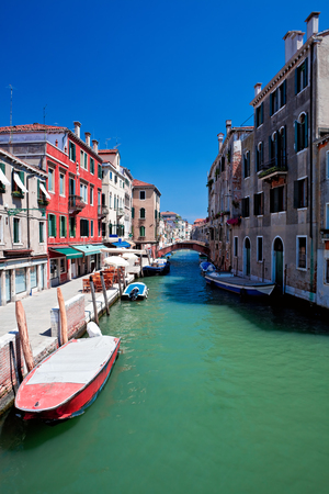 View of beautiful colored venice canal with bridge and houses standing in water Stock Photo