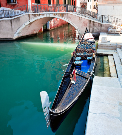 Gondola on colored Venice canal with bridge and houses standing in water