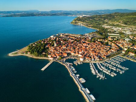 Aerial view of old fishing town Izola in Slovenia, beautiful cityscape with marina at sunset. Adriatic sea coast, peninsula of Istria, Europe.