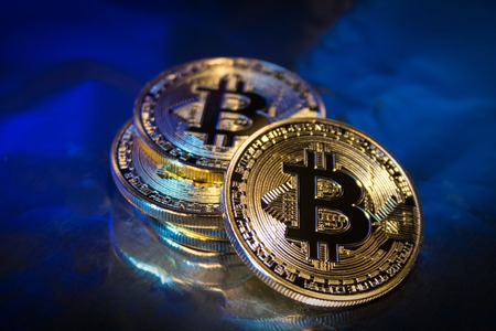 Photo Golden Bitcoins new virtual money Close-up on a blue background. Stock Photo