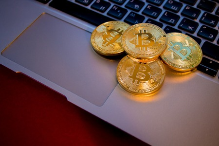 decentralized: Photo Golden Bitcoins On laptop. Trading Concept Of Crypto Currency Stock Photo