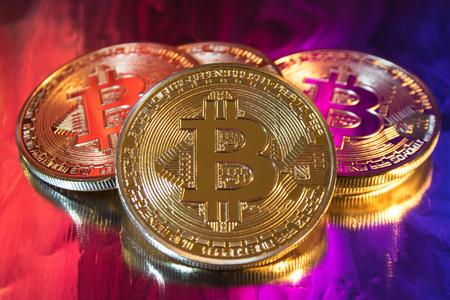 resplandor: Moneda de bitcoin dorada física de criptomoneda en fondo colorido