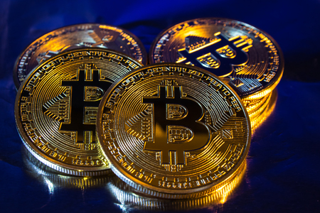 Photo of cryptocurrency physical golden bitcoin coin on colorful background