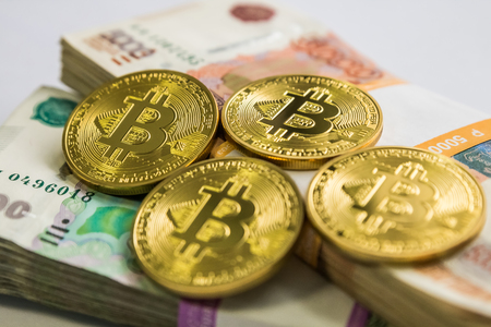 bitcoin gold and the Russian ruble. Bitcoin coin on the background of Russian rubles.
