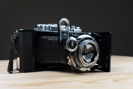 old folding camera on a textured rustic wooden surface.