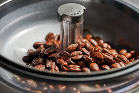 wanderlust: fresh coffee beans in coffee Machine grinders Stock Photo