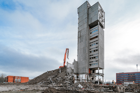 Wide angle panorama of building demolition with hydraulic excavator Stock Photo