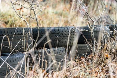 Pile of discarded Old tyres on the grass