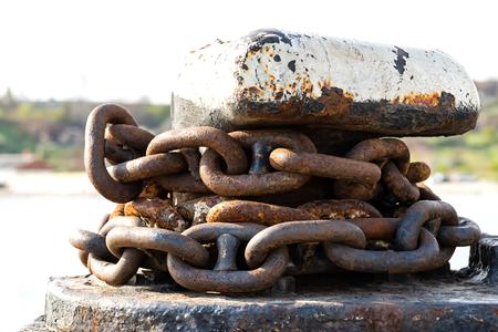 rusty anchor chain around the mooring bollard