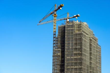 tower crane scaffolding construction high-rise building blue sky Archivio Fotografico