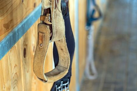 closeup stirrup riding horse equipment hang on wooden fence