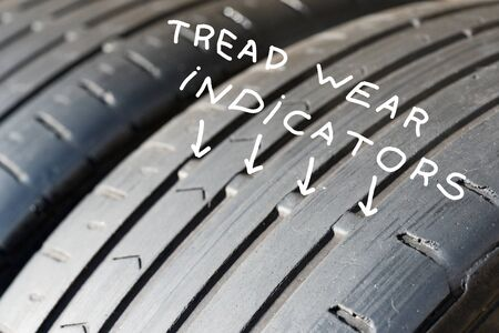 worn out tyre tread wear indicators closeup. the tyres tread has clearly worn down to the legal limit. Archivio Fotografico