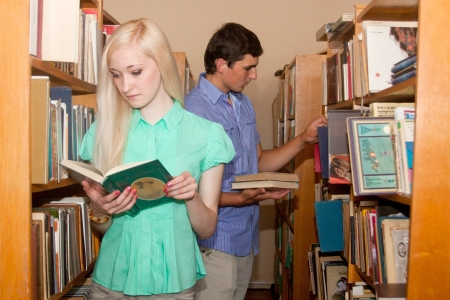 Young man and woman loking for a book in the library photo